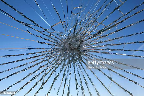 A clear blue sky seen through a shattered glass window
