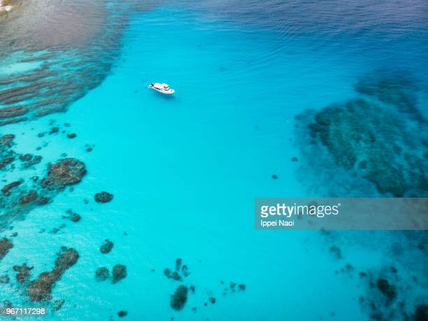 Clear blue tropical water, coral reef and boat from above, Kerama Islands, Okinawa, Japan