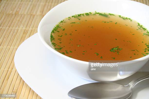 Clear bouillon soup with spoon and plate