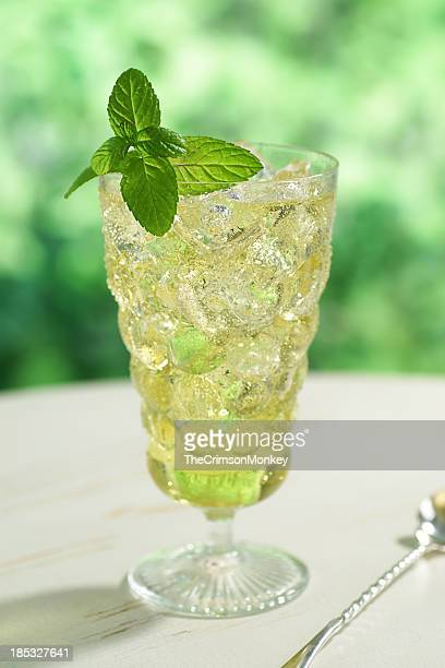 A clear bubble glass full of iced green tea with mint