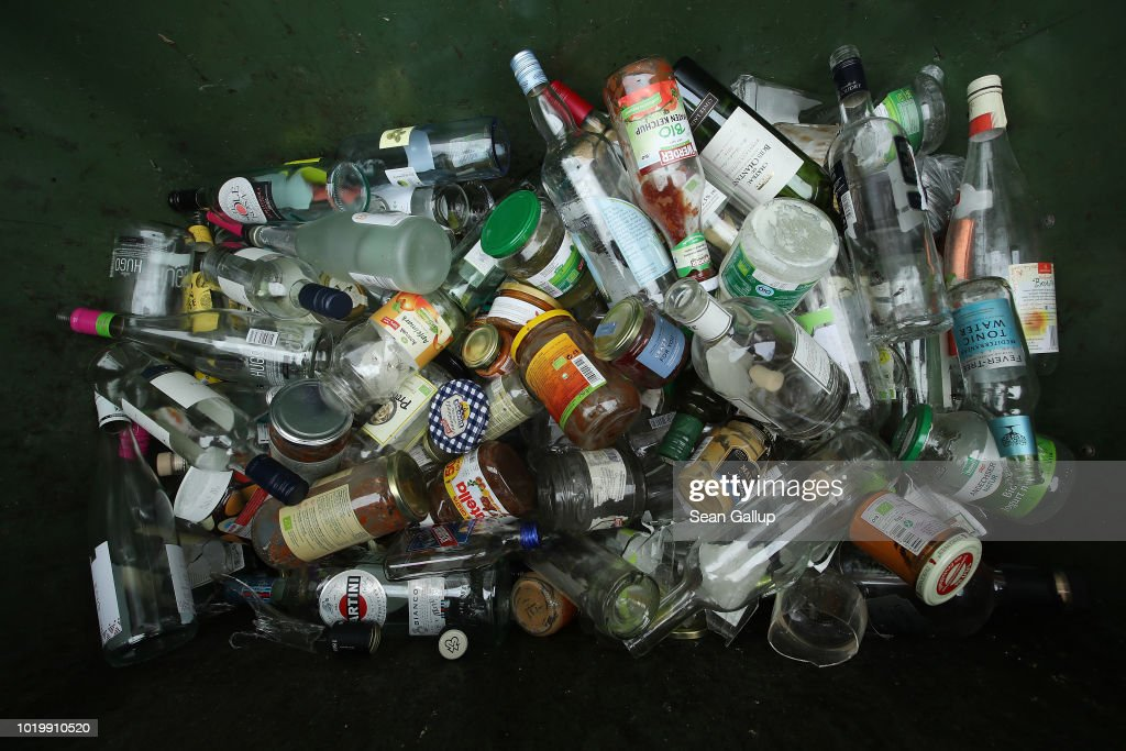 Clear glass bottles and jars lie in a recycling bin on August 20