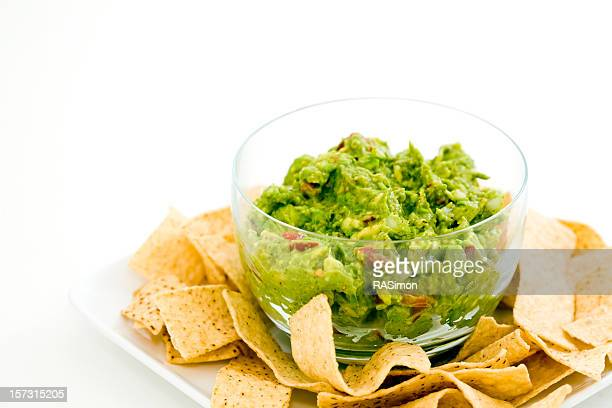 A clear glass bowl of guacamole surrounded by tortilla chips