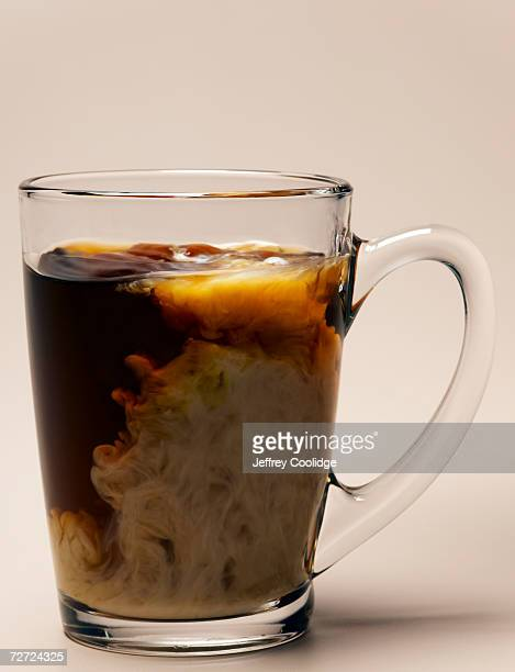 Clear glass cup containing coffee and milk mixing, close-up