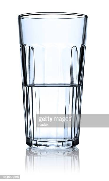 clear glass half full of water isolated with reflection - half full stock photos and pictures