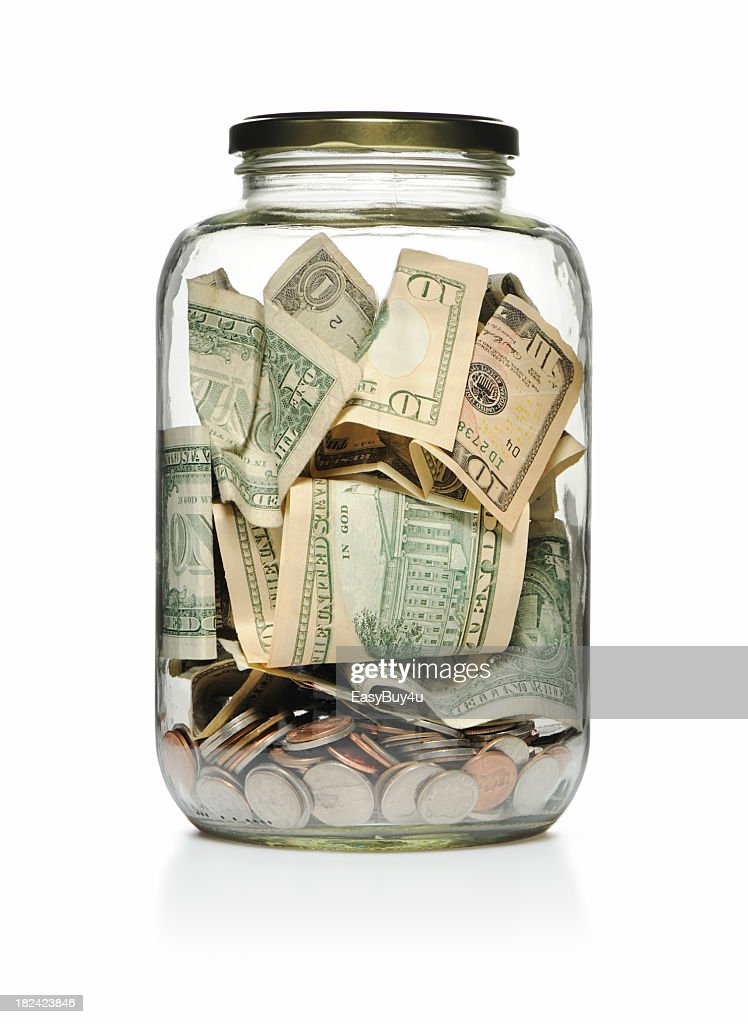A clear glass jar filled with cash and coins  : Stock Photo