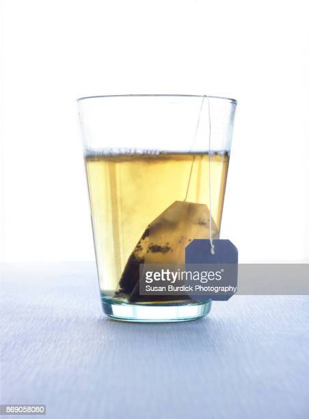 Clear glass with tea and teabag inside and blank tag hanging on a string