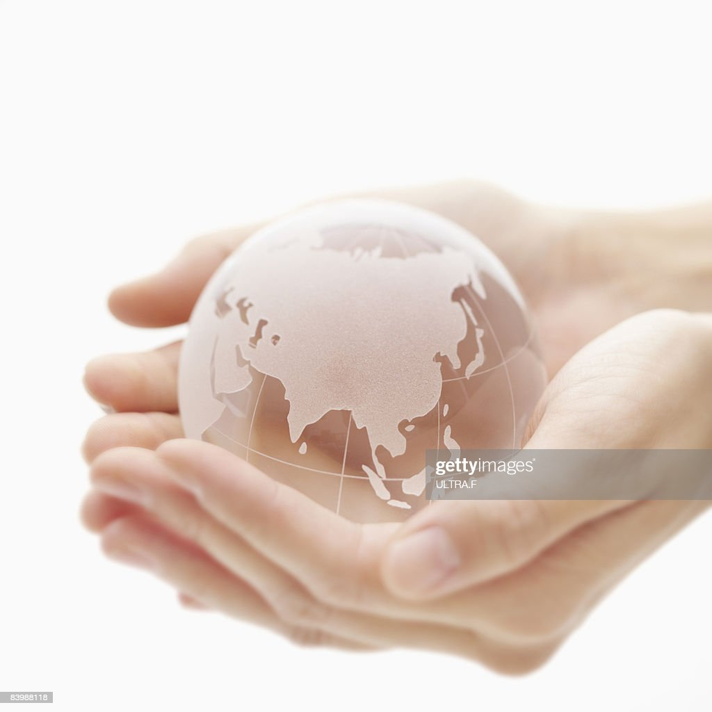 Clear globe is on the palms. : Stock Photo
