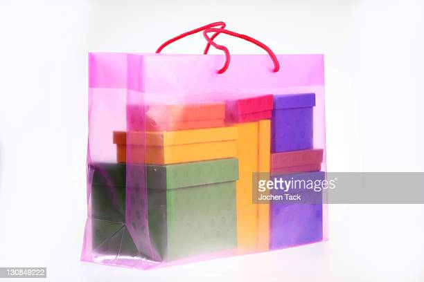 Clear plastic bag filled with colorful paper gift boxes