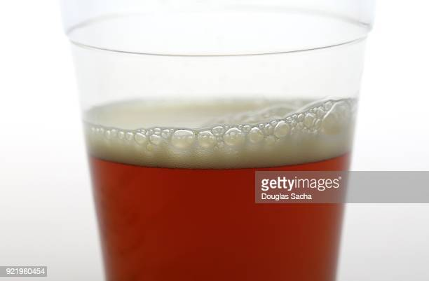 clear plastic cup of a cold beer on a white backgroung - ale stock pictures, royalty-free photos & images
