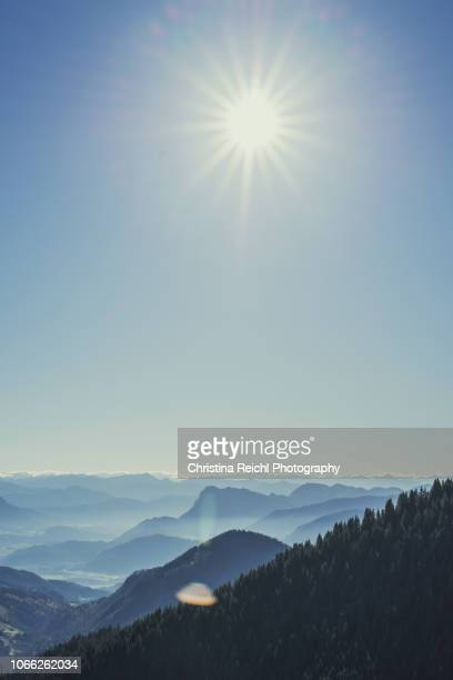 clear sky on a sunny day with fog coming up in the mountains - stimmungsvoller himmel stock-fotos und bilder