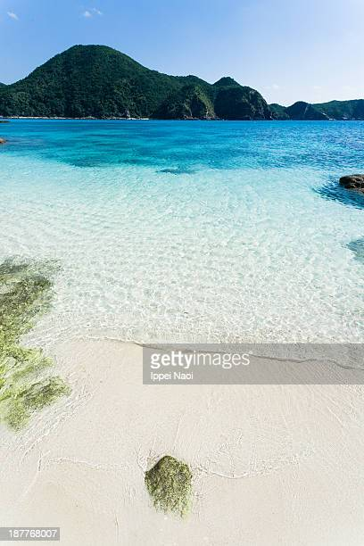 Clear tropical water lapping on white sand beach