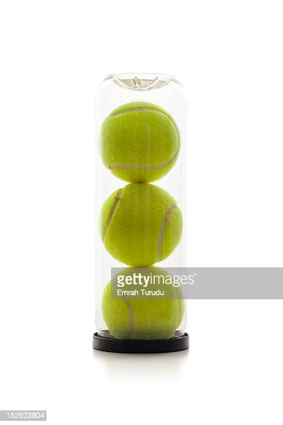 A clear tube of tennis balls