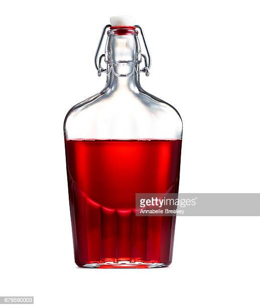 clear vintage bottle with red syrup on white - bottle stopper stock photos and pictures