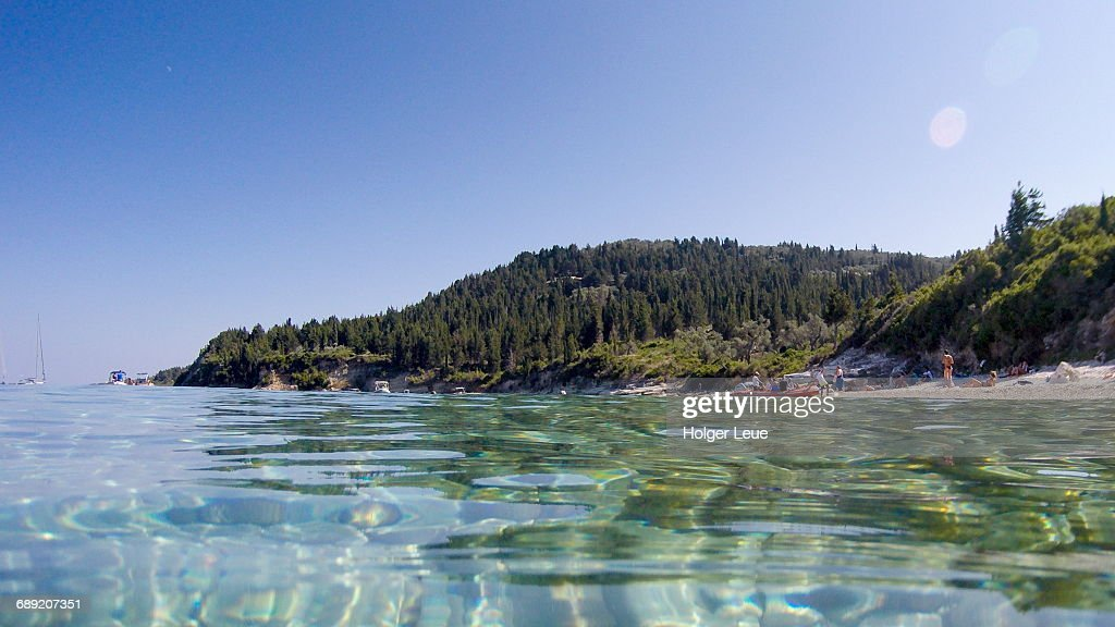 Clear waters, people on beach and coastline : Stock Photo