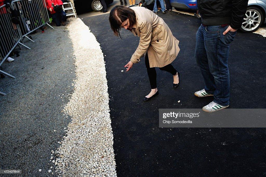 Clearing a path for her boss, a Labour Party campaign staff member moves white stones out of the black asphalt path before Ed Miliband leaves the polling station at Sutton Village Hall in Sutton after casting his vote in the 2015 general election on May 7, 2015 in Doncaster, England. The United Kingdom is going to the polls today to vote for a new government in one of the most closely fought General Elections in recent history.