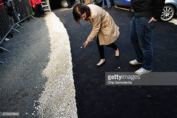 Clearing a path for her boss a Labour Party campaign staff member moves white stones out of the black asphalt path before Ed Miliband leaves the...