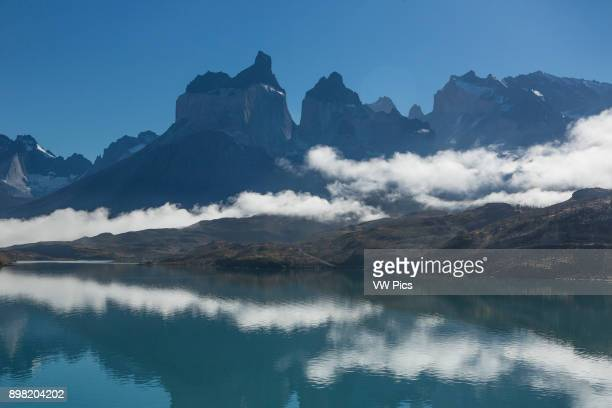 Clearing fog over Lago Pehoe A few low clouds remain obscuring the bases of the Cuernos del Paine To the right of the Cuernos the tops of Torre Sur...