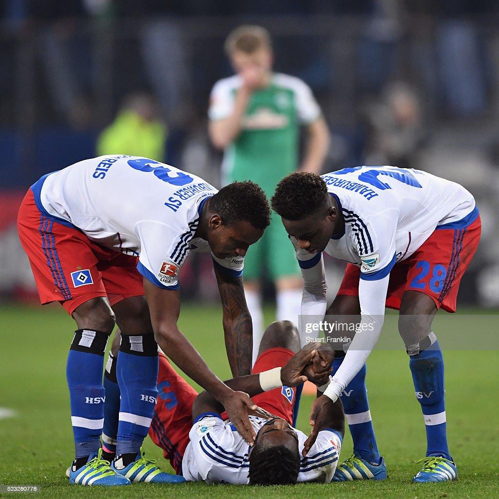 Cleber (L) and Gideon Jung of Hamburg help up their team mate Johan Djourou after the Bundesliga match between Hamburger SV and Werder Bremen at Volksparkstadion on April 22, 2016 in Hamburg, Germany.