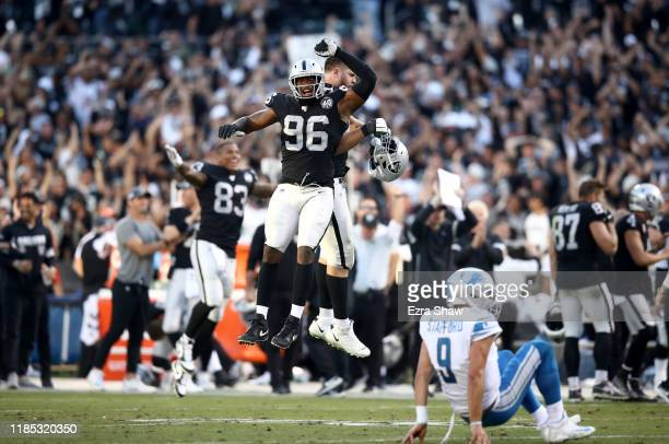Clelin Ferrell and Kolton Miller of the Oakland Raiders react after Matthew Stafford of the Detroit Lions threw an incomplete pass on fourth down to...