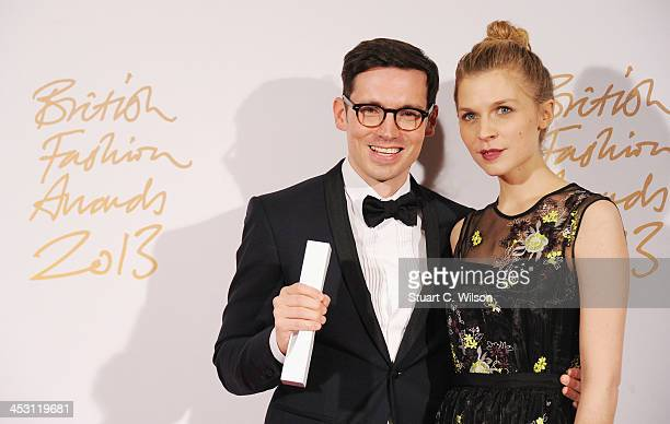 Clemence Poesy and Erdem Moralioglu with the Red Carpet Designer of the Year Award poses in the winners room at the British Fashion Awards 2013 at...