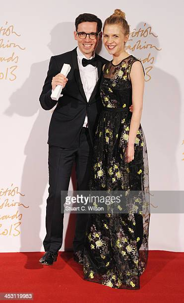 Clemence Poesy and Erdem Moralioglu with the Red Carpet Designer of the Year Award pose in the winners room at the British Fashion Awards 2013 at...