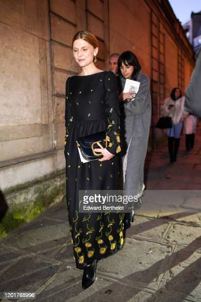 Clemence Poesy wears earrings, a black floral print dress, a Valentino bag, outside Valentino, during Paris Fashion Week - Haute Couture...