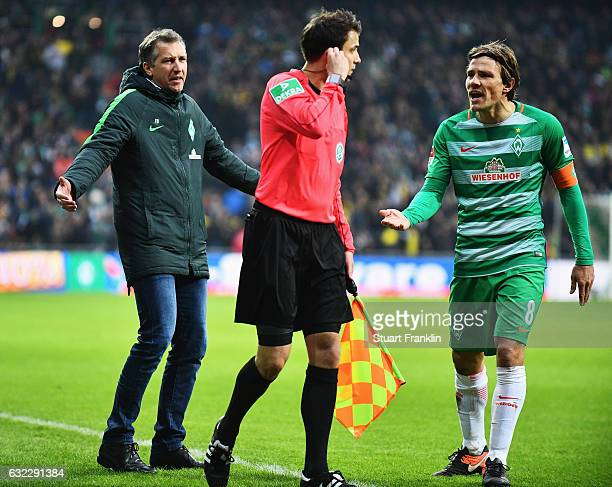 Clemens Fritz and Frank Baumann sports director of Bremen appeal to the referees assistant after the red card during the Bundesliga match between...