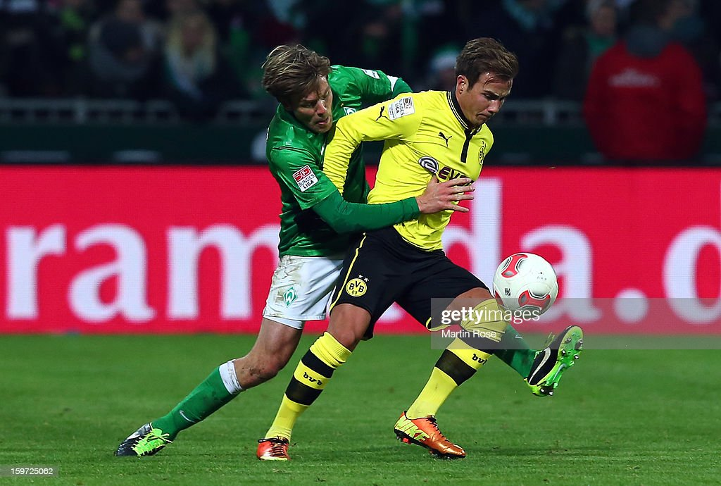 Clemens Fritz (L) of Bremen and Mario Goetze (R) of Dortmund battle for the ball during the Bundesliga match between Werder Bremen and Borussia Dortmund at Weser Stadium on January 19, 2013 in Bremen, Germany.