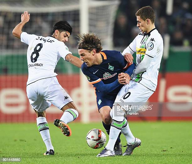 Clemens Fritz of Bremen is challenged by Mahmoud Dahoud and Álvaro Domínguez Soto of Gladbach during the DFB Pokal match between Borussia...