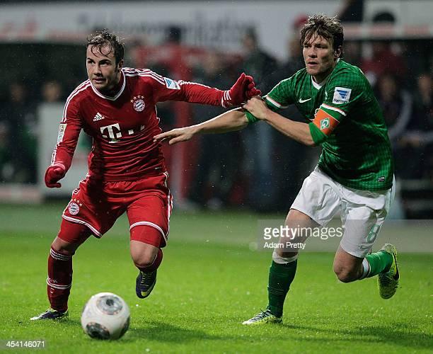 Clemens Fritz of Bremen tackles Mario Goetze of Bayern during the Bundesliga match between Werder Bremen and FC Bayern Muenchen at Weserstadion on...
