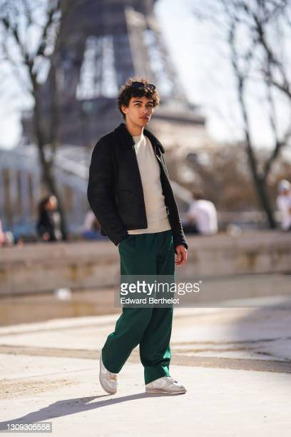 """Clement Cornebize, fashion model, wears sunglasses, a beige wool pullover from APC, a black aviator jacket from """"YMC - You Must Create"""", green jogger..."""