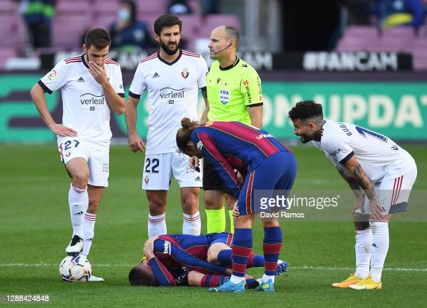 Clement Lenglet of Barcelona lies injured and is checked on by Antoine Griezmann of Barcelona during the La Liga Santander match between FC Barcelona...
