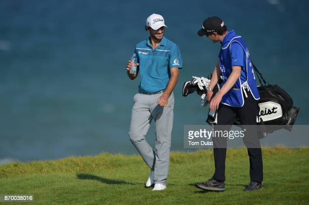 Clement Sordet of France walks to the 18th green with his caddie during the final round of the NBO Golf Classic Grand Final at Al Mouj Golf on...