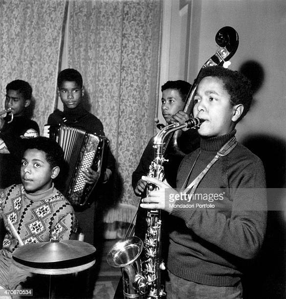 'Clemente Menditto 14 years old playing saxophone together with his friends a band of young musicians testing themselves with musical instruments at...
