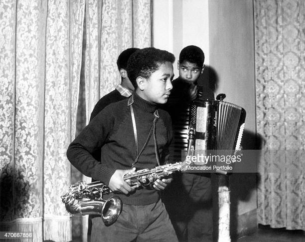'Clemente Menditto 14 years old wields a saxophone testing himself with music together with two friends into a band of mulatto kids at the Village of...