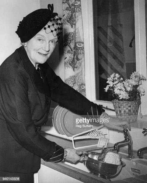 Clementine Churchill wife of Prime Minister Winston Churchill washes a cauliflower in a kitchen sink at the People's House at the Ideal Home...