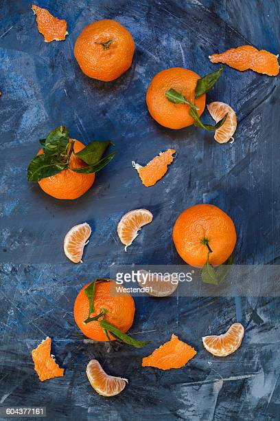 Clementines on blue background, peeled