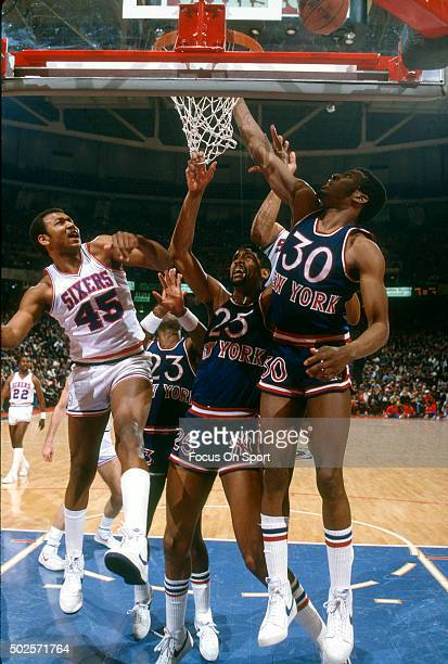 Clemon Johnson of the Philadelphia 76ers battles for a rebound with Bernard King and Bill Cartwright of the New York Knicks during an NBA basketball...