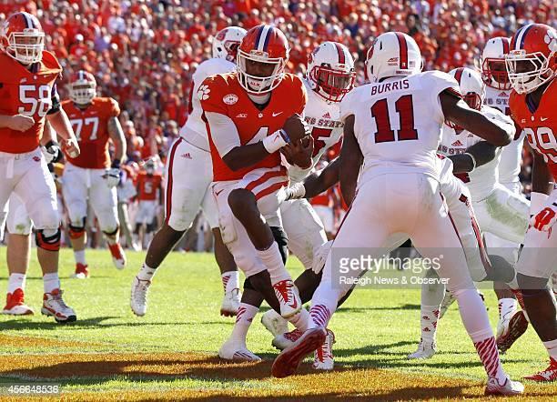 Clemson quarterback Deshaun Watson gets past North Carolina State cornerback Juston Burris to score on a 3yard touchdown run during the first half at...