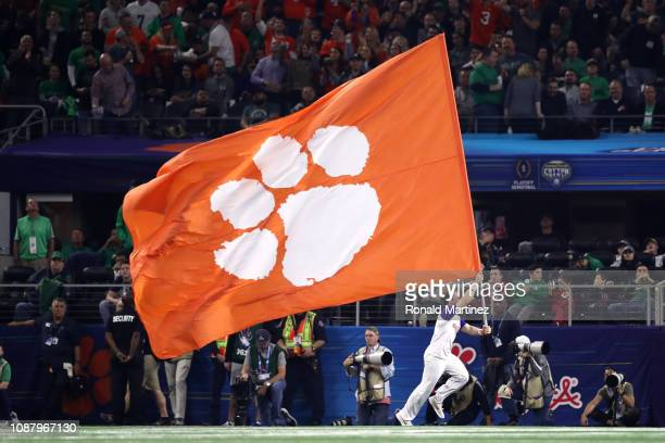 Clemson Tigers cheerleader runs with a flag in the first half against the Notre Dame Fighting Irish during the College Football Playoff Semifinal...