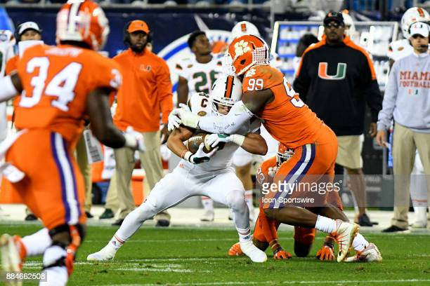 Clemson Tigers defensive end Clelin Ferrell tackles Miami Hurricanes wide receiver Braxton Berrios on the play during the ACC Championship game...