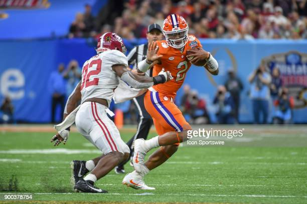 Clemson Tigers quarterback Kelly Bryant prepares to stiff arm Alabama Crimson Tide linebacker Rashaan Evans as he cuts to the outside during the...