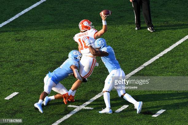 Clemson Tigers quarterback Trevor Lawrence gets rid of the ball before getting sacked by n212d and North Carolina Tar Heels linebacker Tomon Fox in...