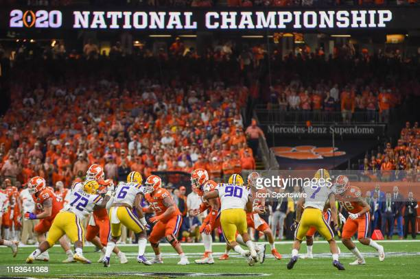 Clemson Tigers quarterback Trevor Lawrence looks to fake a handoff as LSU Tigers defensive lineman Rashard Lawrence provides pressure during the CFP...