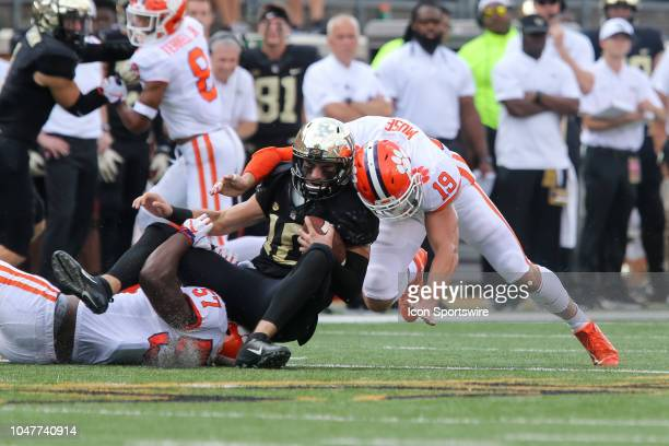 Clemson Tigers safety Tanner Muse and linebacker Tre Lamar tackle Wake Forest Demon Deacons quarterback Sam Hartman on October 6 2018 at BBT Field in...