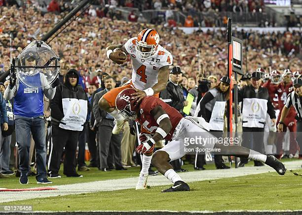 Clemson University quarterback Deshaun Watson goes airborne as he is tackled by University of Alabama defensive back Ronnie Harrison during second...