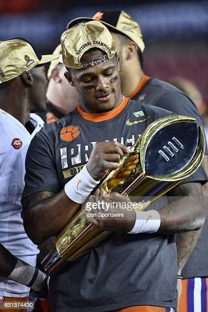 Clemson University quarterback Deshaun Watson has a moment with the National Championship trophy during the award ceremony after the second half of...