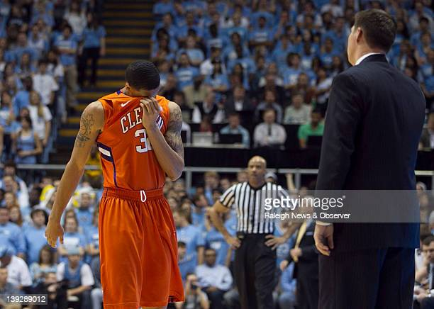 Clemson's KJ McDaniels wipes his face with his uniform as he readies for a conference with head coach Brad Brownell after the Tigers fell behind by...