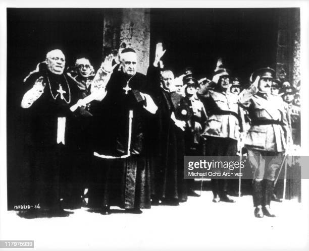 Clergy and soldiers salute in a scene from the film 'To Die in Madrid' aka 'Mourir a Madrid' 1965
