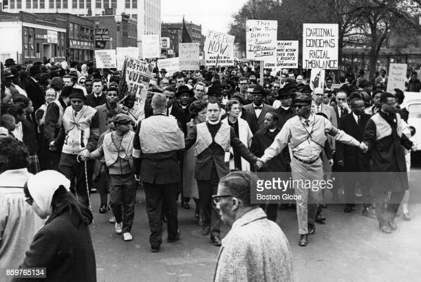 Clergy members stand in front as a crowd protesting for civil rights moves toward the Boston Common in Boston April 23 1965